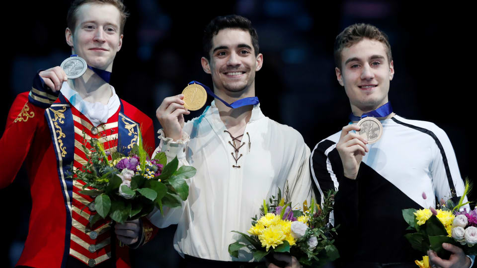 Spain's Javier Fernandez celebrates winning the Men's Free Skating with second placed Russia's Alexander Samarin and third placed Italy's Matteo Rizzo on the podium